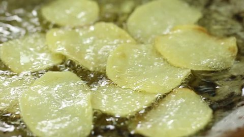 Deep fried golden potato chips in oil, close up