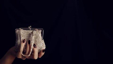 Woman hand holding vintage elegance-handbag decorated  with diamond isolated on black background. Handbag made of diamonds. Female sparkling glamour luxury silver diamond purse handbag.