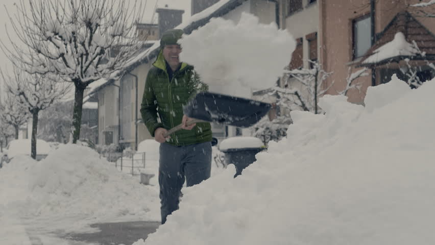 FS of a man shoveling in front of houses. | Shutterstock HD Video #1015165252