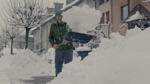 FS of a man shoveling in front of houses.