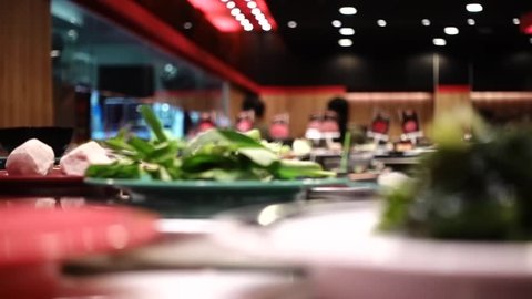 Conveyor Belt Shabu Shabu hotpot transporting food and ingredients in restaurant. Shabu ou Sukiyaki ingredients i.e. meat, vegetables and etc. are on the Conveyor system in the restaurant.