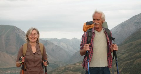 Positive mature caucasian couple trekking in mountains with backpacks, enjoying their adventure 4k