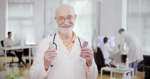 Elderly man doctor recommends vitamins for men to increase erection and male potency at any age, looking at camera and smiling