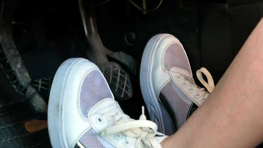 Girl on white sneakers shoes pressing car pedals 4k