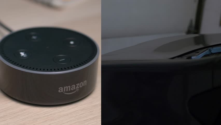 MONTREAL, CANADA - August 2018 : Amazon Echo Alexa Dot opening a garage door of a house. Voice activated intelligent assistant