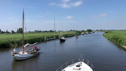 Sailboat sailing towards the bridge and the langweerder wielen lake in Friesland, The Netherlands