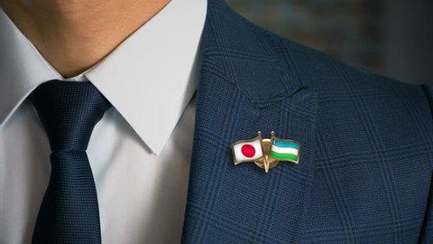 Businessman Walking Towards Camera With Friend Country Flags Pin Japan - Uzbekistan