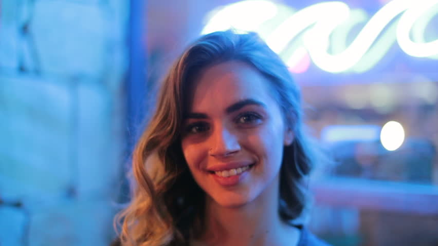 Young woman smiling to camera at night next to neon light. Nightlife atmosphere of girl looking to camera