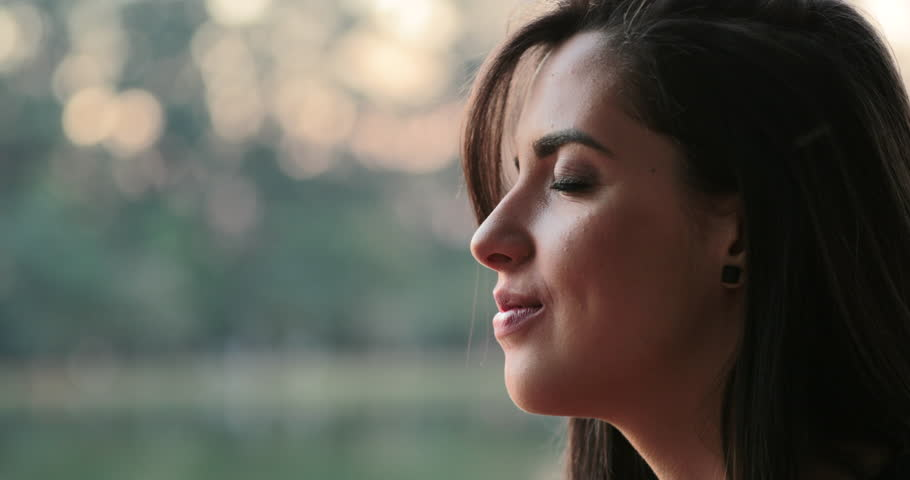 Young woman with eyes closed taking a deep breath outside at the park | Shutterstock HD Video #1015310152