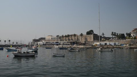 Fishing boats on Cascais bay with the stronghold fort in background.