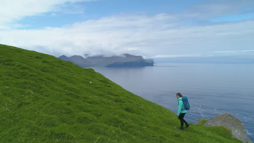 AERIAL, COPY SPACE: Young woman hikes up a grassy hill in Faroe Islands overlooking the endless blue ocean. Flying over female hiker during her ascent to one of the peaks with picturesque view of sea.