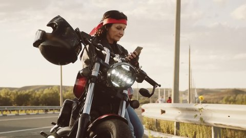 Biker granny in a leather jacket and gloves, a red scarf on his head, sitting on his cool motorcycle. Visible hanging on the steering wheel helmet. The woman is actively using a smartphone.