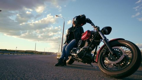 An elderly biker woman in a leather jacket and gloves sitting on a motorcycle in the background of an empty road. The woman is visible from different sides, she looks into the distance. The life of an