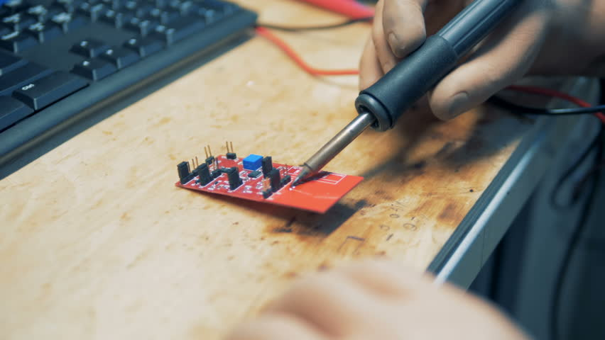 Close up of a soldering iron in a prosthetic hand at work | Shutterstock HD Video #1015314472