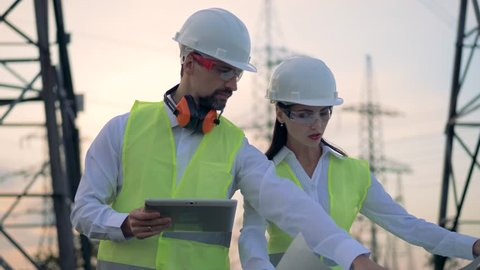 Male and female engineers in hard hat discussing construction project during energy substation inspection.