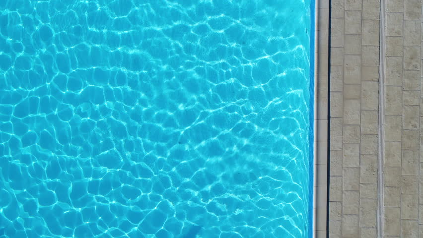 Man diving in a swimming pool, sunny day France. Aerial vertical view.