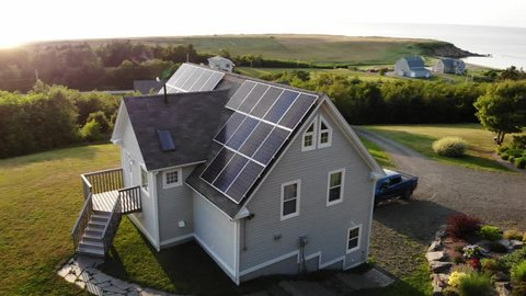 An aerial shot of a beautiful cottage home on the coast in cape breton nova scotia with solar panels