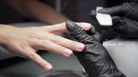 Beautician grinds the nail bar for a manicure in the beauty salon. Finger nail treatment, grinding and polishing. Manicurist Hands Make Female manicure with nail clippers in the nail Salon.
