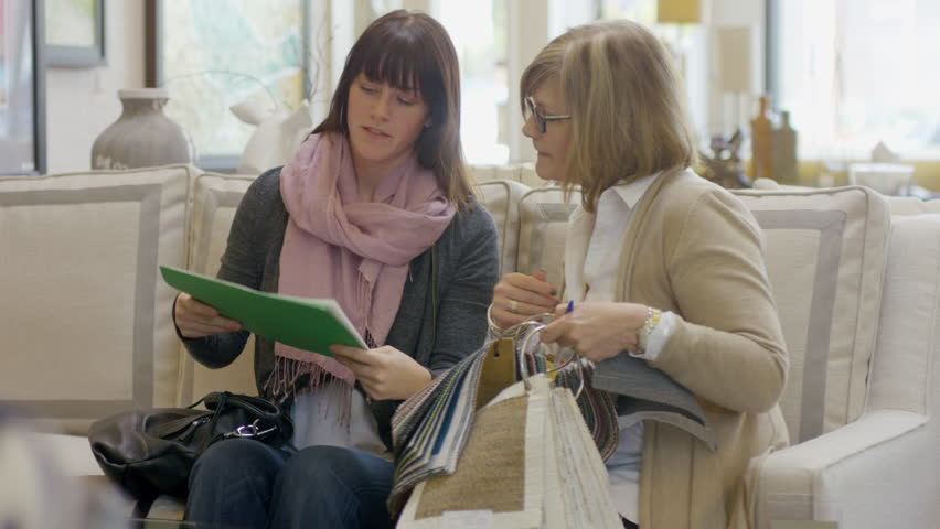 Handheld Shot Of Owner Talking To Customer At Furniture Store