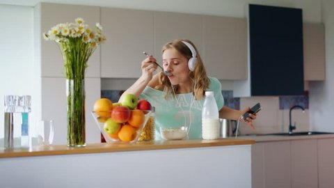 Happy woman eating cornflakes breakfast in morning. Woman eat breakfast health and having fun listening music in headphones. Smiling girl dancing in kitchen at home. Good morning music