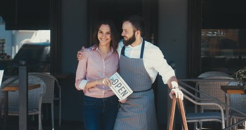 Two mid 30s Caucasian male and female business partners or couple standing with an open sign near their small cafe, smiling and looking into camera. Small business concept. 4K UHD 60 FPS SLOW MOTION