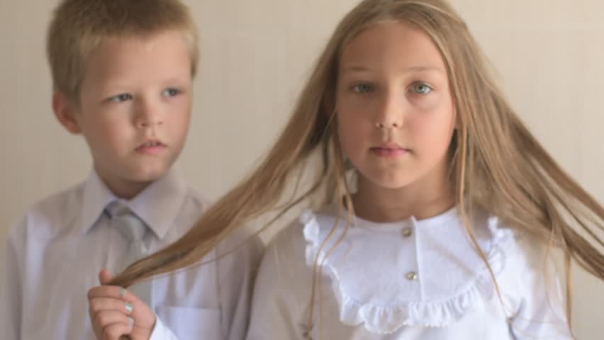 Close-up portrait of happy children with blue eyes and blond hair in school uniform. Boy and girl preschoolers on wind. Breeze plays with girl's hair and clothers. Old vintage style. Shallow focus | Shutterstock HD Video #1015393012