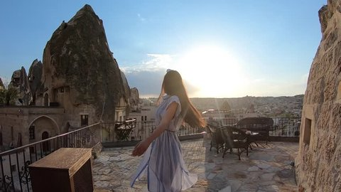Young beautiful woman walking in front of Cappadocia landscape at sunset. Turkey.