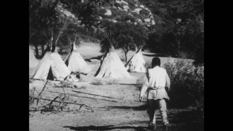 1950s: Forest, large boulder, rushing river, Native American man walks back to camp with teepees, people. People tend land, lay brush onto fire.
