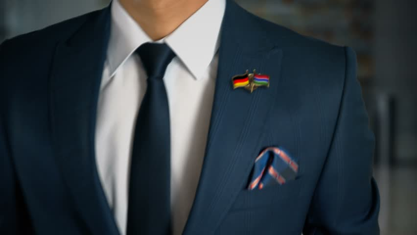 Businessman Walking Towards Camera With Friend Country Flags Pin Germany - Gambia