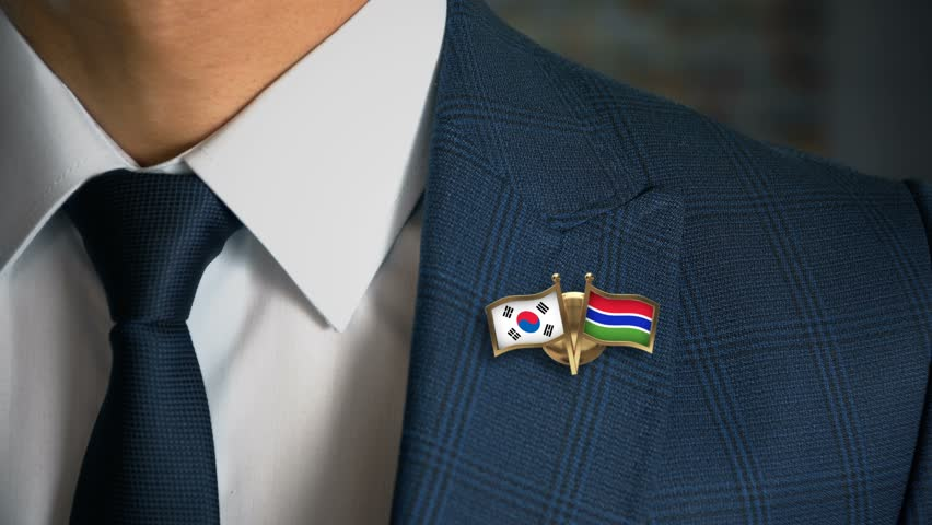 Businessman Walking Towards Camera With Friend Country Flags Pin South Korea - Gambia