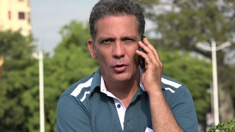 Serious Adult Hispanic Man Using Cell Phone
