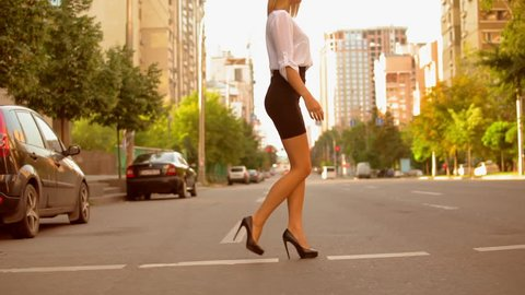 Side view fashionable woman with blond hair wearing white shirt and black skirt and high-heels shoes walking on the road in summer city.slow motion