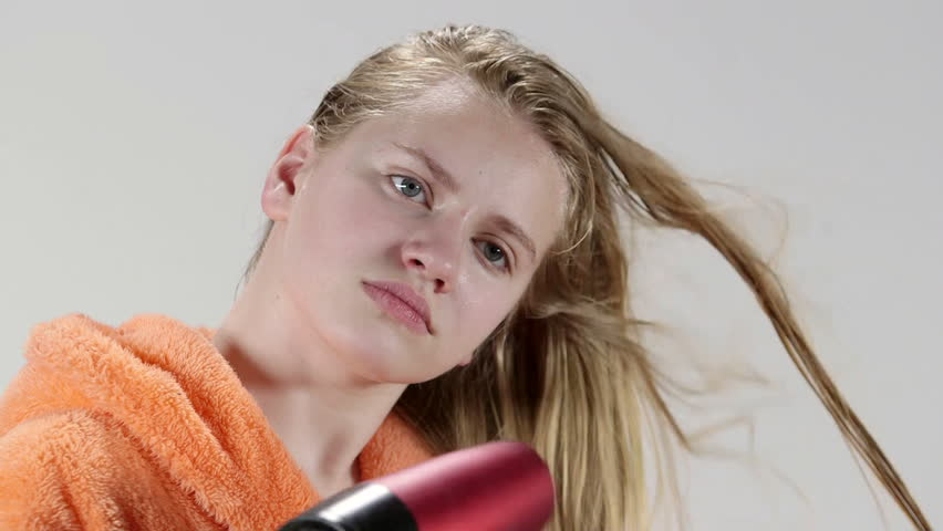 Teenage girl drying long hair after bath with hair dryer.