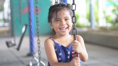 Asian child cute or kid girl smile laugh playing old swing and happy fun or cheerful enjoy on holiday relax with exercise at playground or amusement public park and nursery kindergarten school on slow