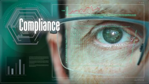A close up of a businessman eye controlling a futuristic computer system with an Compliance concept.