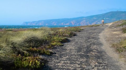 Mature man (55-60) cycles along a bumpy asphalt path overlooking Praia do Guincho and Roca do Cabo near Cascais, Portugal during a windy summer day