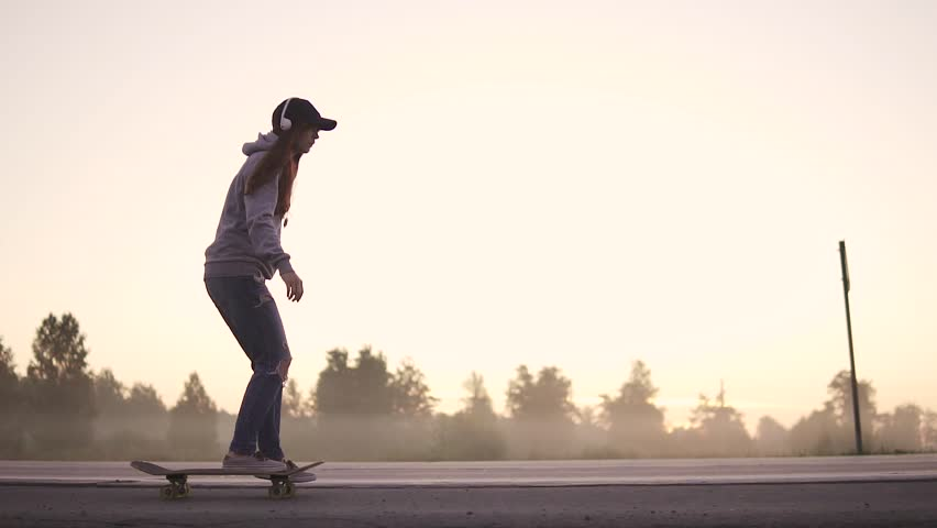 silhouette of a girl skating on a skateboard on a deserted highway at sunset. slow motion.