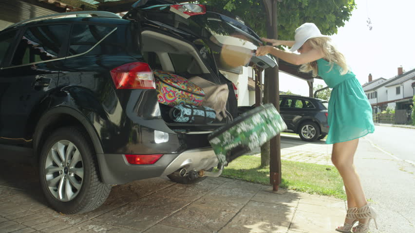 LENS FLARE: Lighthearted young woman fails to close the trunk of her black car and her suitcases fall all over the driveway. Female tourist fails to catch travel bags falling from the back of SUV.
