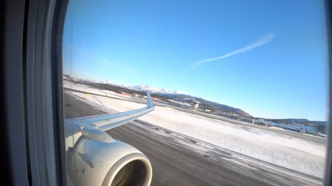 Airplane taking off from Harstad/Narvik Evenes Airport in Northern Norway in the Arctic Circle during a beautiful winter day.