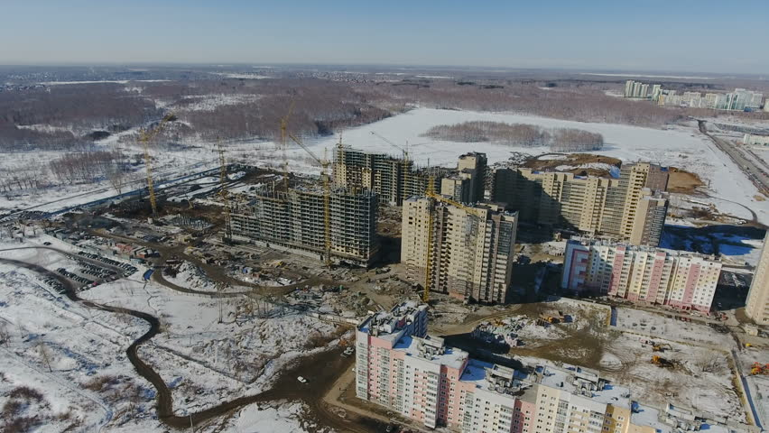 Construction of a new residential area in front of road traffic covered in snow. | Shutterstock HD Video #1015542352