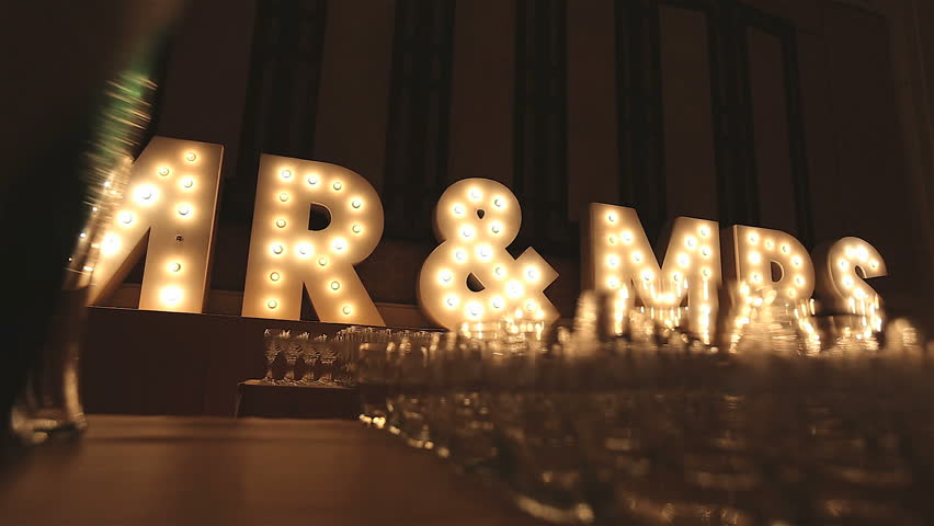 Retro lIghtbox theater style of text Mr & Mrs decoration on the backdrop in the wedding reception dinner night party with a group of wine glasses blurry in foreground, Low angle, Dolly slider scene. | Shutterstock HD Video #1015566382