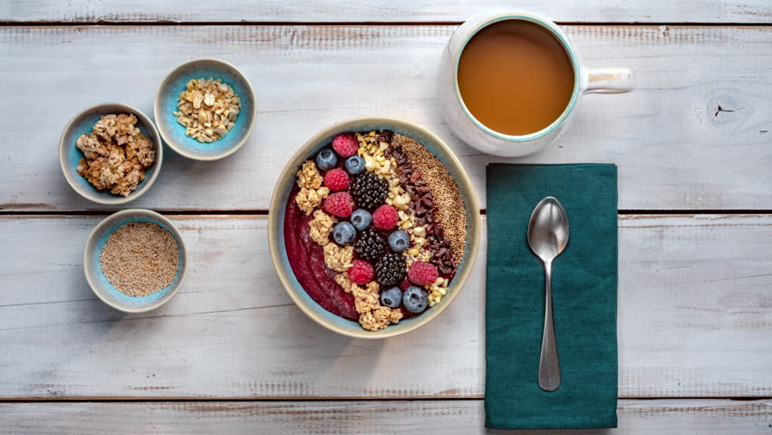 Healthy Breakfast - Smoothie Bowl with berry fruits, nuts, granola and a cup of coffee #1015569562