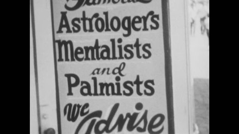 1960s: UNITED STATES: Famous Astrologers, Mentalists, and Palmists advertising board. Fairground attractions. Posters at fair