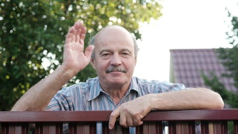 Friendly caucasian old man waving hi or farewell, isolated outdoors background with green trees and fence. Homeowmer saying goodbye to his guest