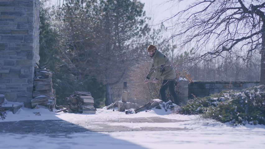 Young bearded man chopping wood outside in the winter on a sunny day. Wide shot. Shot with a RED camera. 4k footage.