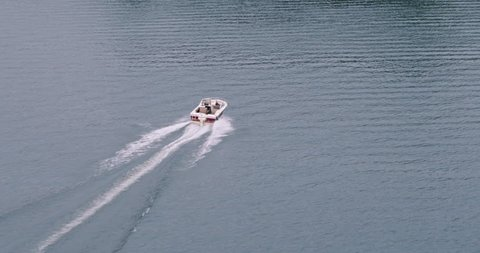 Drone shot of millennial driving outboard motor boat across rough lake