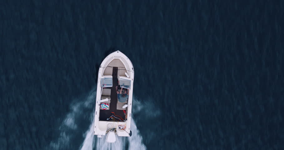Direct overhead shot of young man driving outboard motor boat across glassy lake