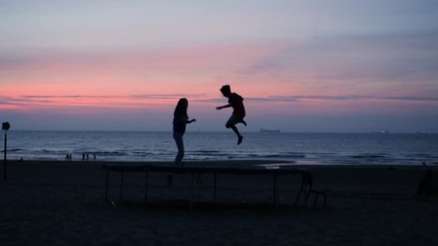 Cinematic slow motion of happy child friends smiling kids bouncing jumping on trampoline at the sunset on the beach - best memories ever for friends and families - blue sky