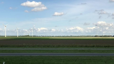 Zwolle / The Netherlands - August 26th 2018: View from Intercity train window to dutch countryside. Some cars passing by as the landscape with large wind generators or windmills.