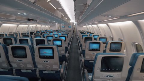 Steadicam shot of walking through the empty economy class in the airplane. Rows of seats with working seat monitors